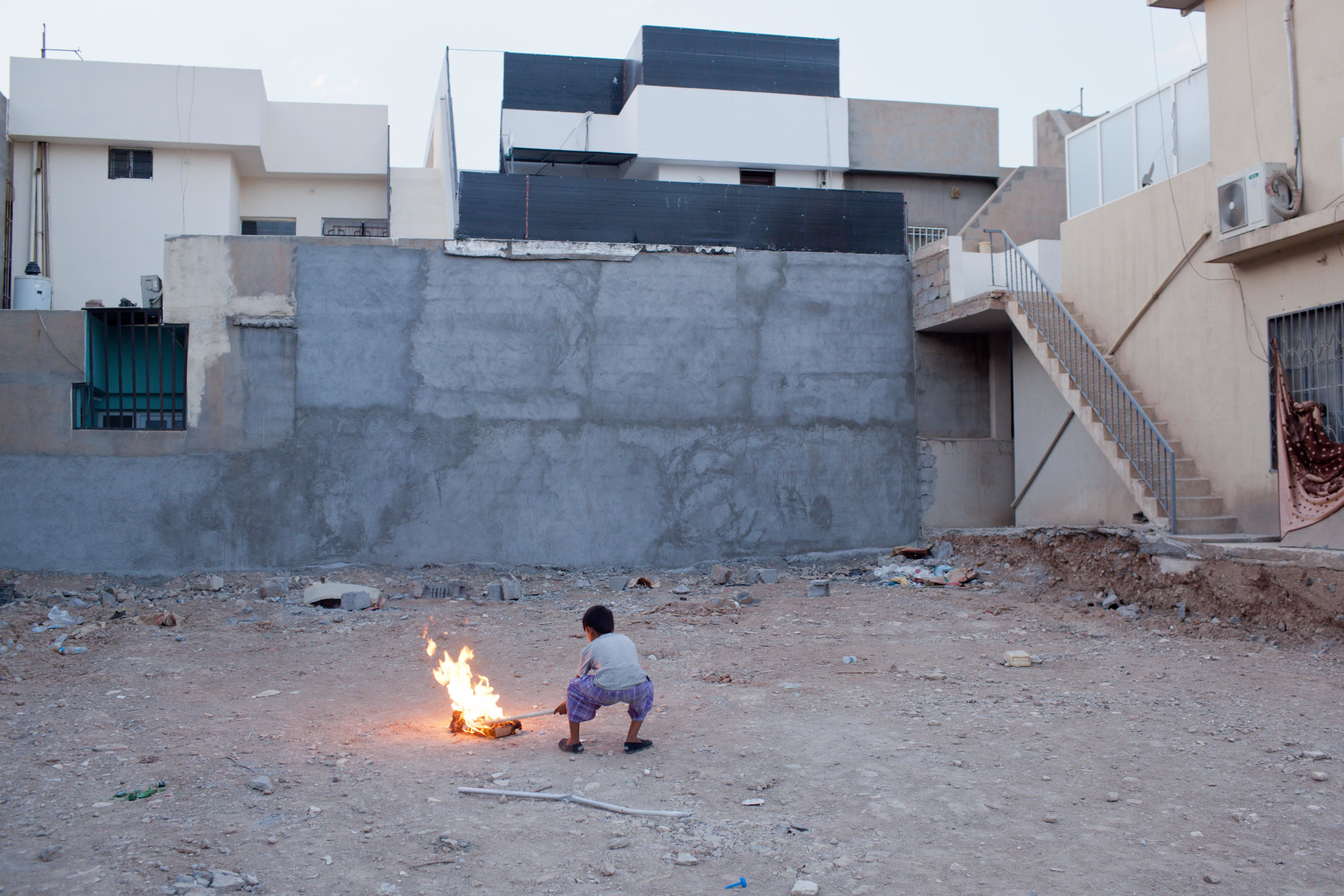 ERBIL, IRAQ: A young boy plays with burning garbage in an abandoned lot across the street from a camp for displaced Christians where he lives with his family. Photograph by Sebastian Meyer