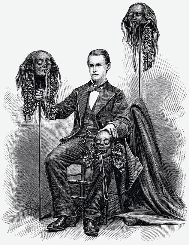 Ernest Morris, an explorer of South America, poses with shrunken heads from the upper Amazon, 1877 © Granger, New York City