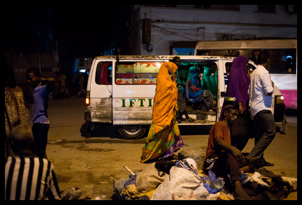 Men and women walk through the bus station and market in Djibouti City, Djibouti on May 13, 2015. Djibouti has recieved scores of Yemeni refugees and migrants since the beginning of April. Photograph by Alex Potter
