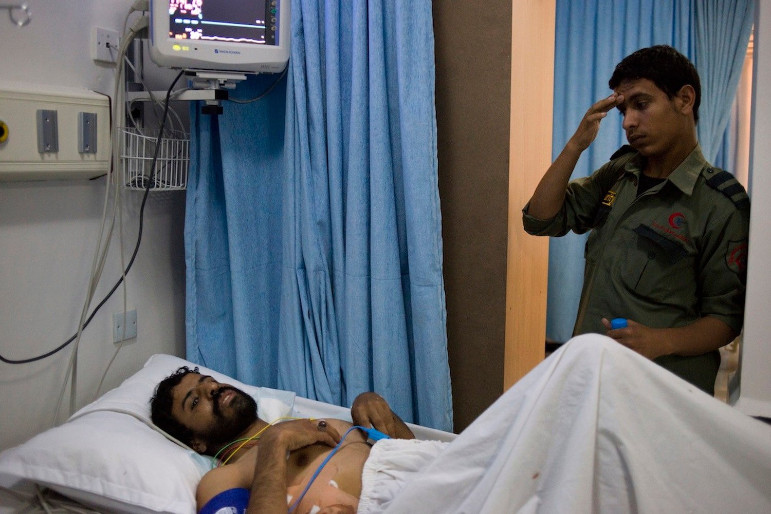 A Yemeni man lies in Moaiyed Hospital after being shot by state security forces at a Houthi protest camp in Sana'a.