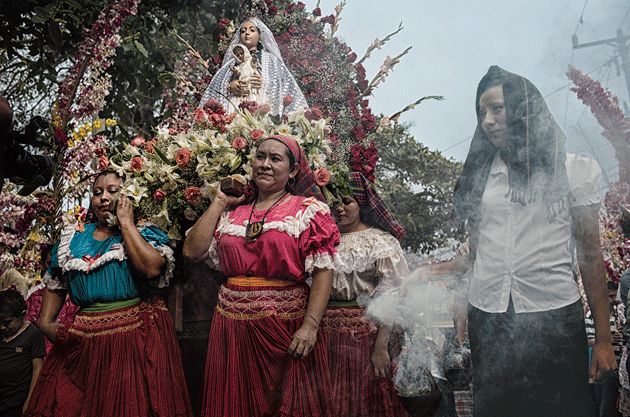Women carry a statue of the Virgin Mary during the annual Flower and Palm Festival, in the town of Panchimalco